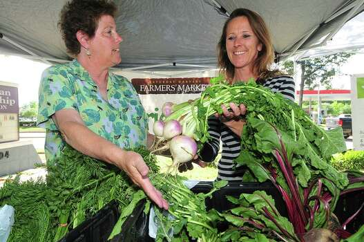 Janice McIntosh and Stacey Mauch offer produce from Georgia's Farm to Market at their booth in the Spring Branch Farmers Market. Photo: Â Tony Bullard 2013, Freelance Photographer / © Tony Bullard & the Houston Chronicle