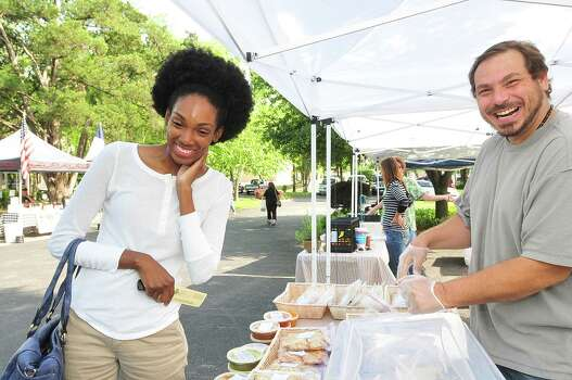 Sherriel Miller samples the chicken samosa offered by Wesley Matteson at the Spring Branch Farmers Market. Photo: Â Tony Bullard 2013, Freelance Photographer / © Tony Bullard & the Houston Chronicle