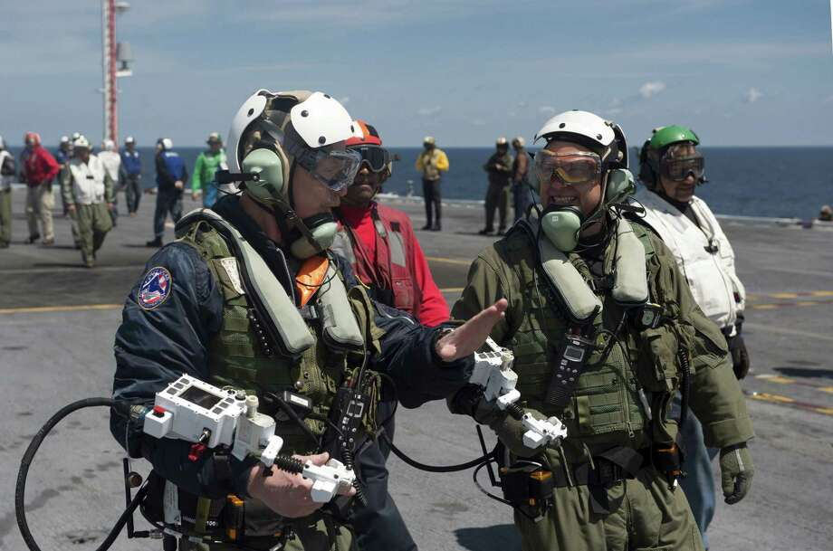 In this handout released by the U.S. Navy, Dave Lorenz, left, and Bruce McFadden, deck operators for Northrop Grumman, discuss the launch of an X-47B Unmanned Combat Air System (UCAS) demonstrator on the flight deck of the aircraft carrier USS George H.W. Bush (CVN 77) May 14, 2013 in the Atlantic Ocean. Lorenz and McFadden operated the X-47B as it taxied from the aircraft elevator to the catapult. George H.W. Bush is scheduled to be the first aircraft carrier to catapult-launch an unmanned aircraft from its flight deck. The Navy plans to have unmanned aircraft on each of its carriers to be used for surveillance and be armed and used in combat roles. Photo: U.S. Navy, Getty Images / 2013 U.S. Navy