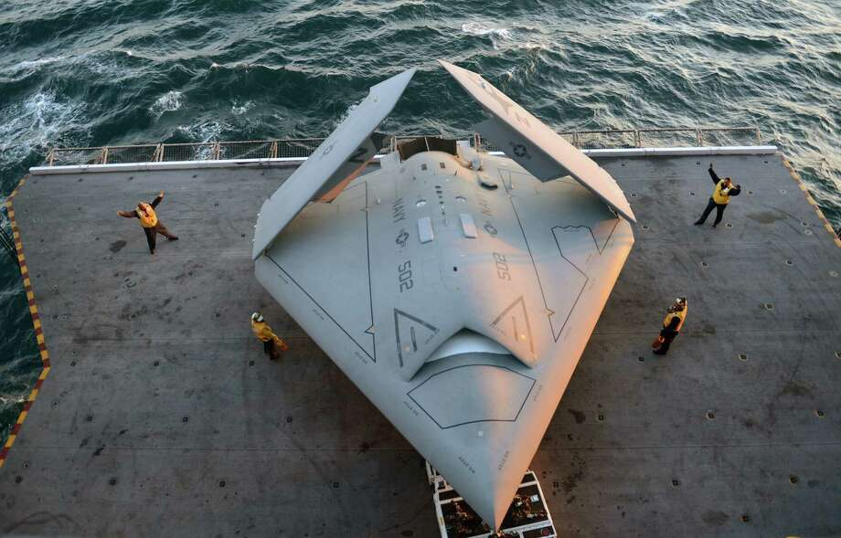 In this handout released by the U.S. Navy, Sailors move an X-47B Unmanned Combat Air System (UCAS) demonstrator onto an aircraft elevator aboard the aircraft carrier USS George H.W. Bush (CVN 77) May 14, 2013 in the Atlantic Ocean. George H.W. Bush is scheduled to be the first aircraft carrier to catapult-launch an unmanned aircraft from its flight deck. The Navy plans to have unmanned aircraft on each of its carriers to be used for surveillance and be armed and used in combat roles. Photo: U.S. Navy, Getty Images / 2013 U.S. Navy
