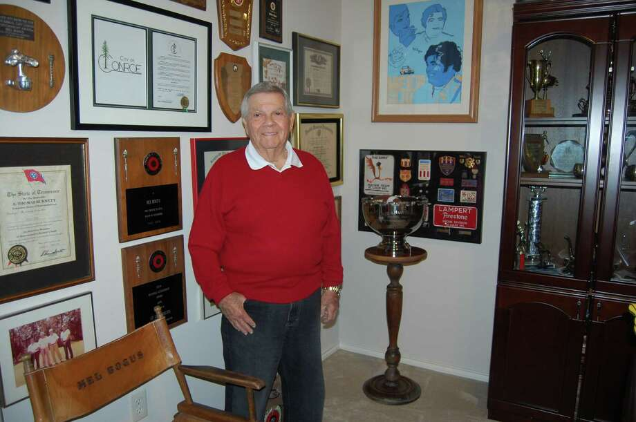 Mel Bogus at his home office, filled with awards, trophies, plaques and honorable mentions. He is surrounded by medals of honor and on one side of his office hang dozens of baseball hats.