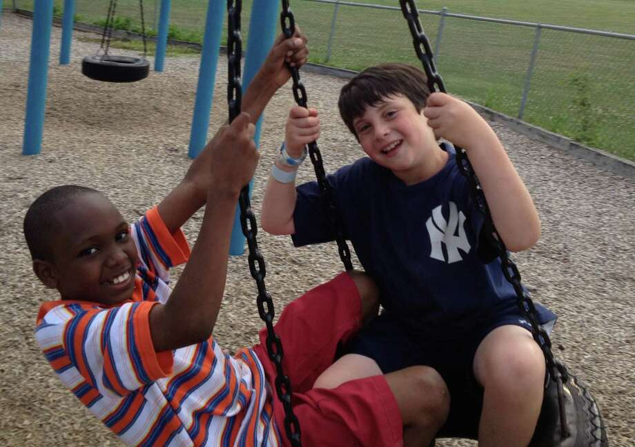 Donte McKenzie, a 9-year-old boy from Brooklyn, N.Y., and Tobey Sappern play on a tire swing last summer on the playground at Fairfield's Roger Sherman Elementary School. The Sappern family of Fairfield hosted McKenzie for a week last August through the Fresh Air Fund program and plan on taking him again for another week this August. Photo: Contributed Photo