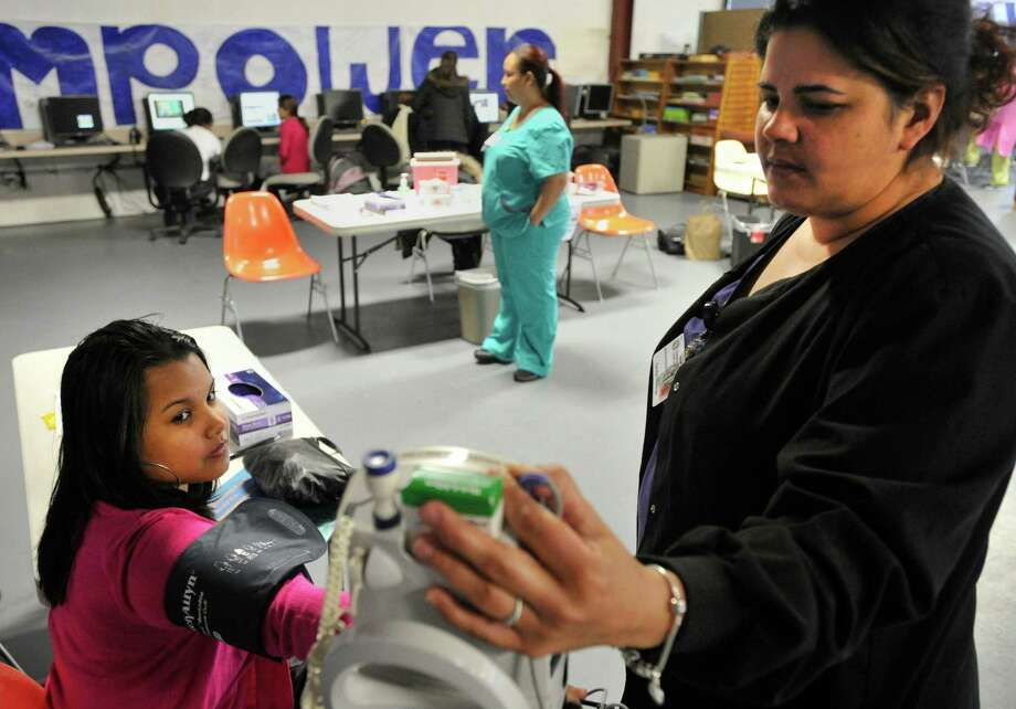 Lesmi Barrientos, left, gets her blood pressure checked by Carolyn Marengo, a medical assistant with Community Health Center Inc., during the second annual Health Day at Neighbors Link Stamford on Monday, March 25, 2013. Franklin Street Community Health Center co-sponsored the event with Neighbors Link Stamford to provide area residents basic health and dental care along with resources on staying healthy. Photo: Jason Rearick / The  Stamford Advocate