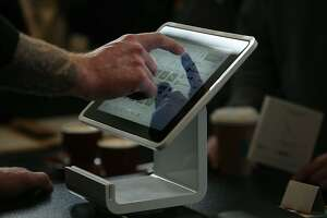 Head barista Stephen Davidson uses the Square Stand, a new point of sale device, at Blue Bottle in San Francisco, Calif., on Tuesday, May 14, 2013.   The Stand hardware secures an iPad with an integrated credit card reader and has plug ins for barcode scanners, customer receipts, and other merchant needs.