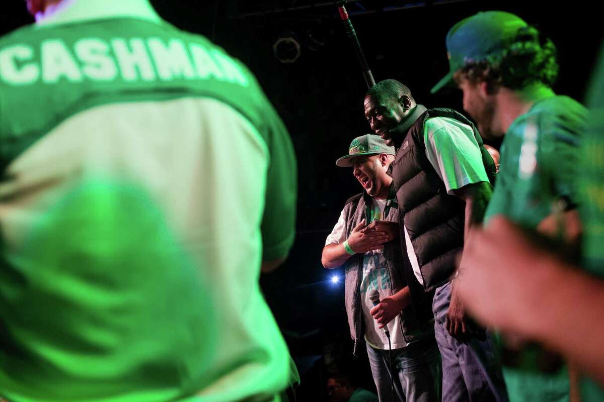 Shawn Kemp, center right, shares a laugh with rapper Neema, center, from the stage during a Bring Our Sonics Back rally and concert Monday, May 13, 2013, at Neumos in Seattle. The free event featured such local hip hop artists as Geo, Grynch, Nacho Picasso and Dyme Def.