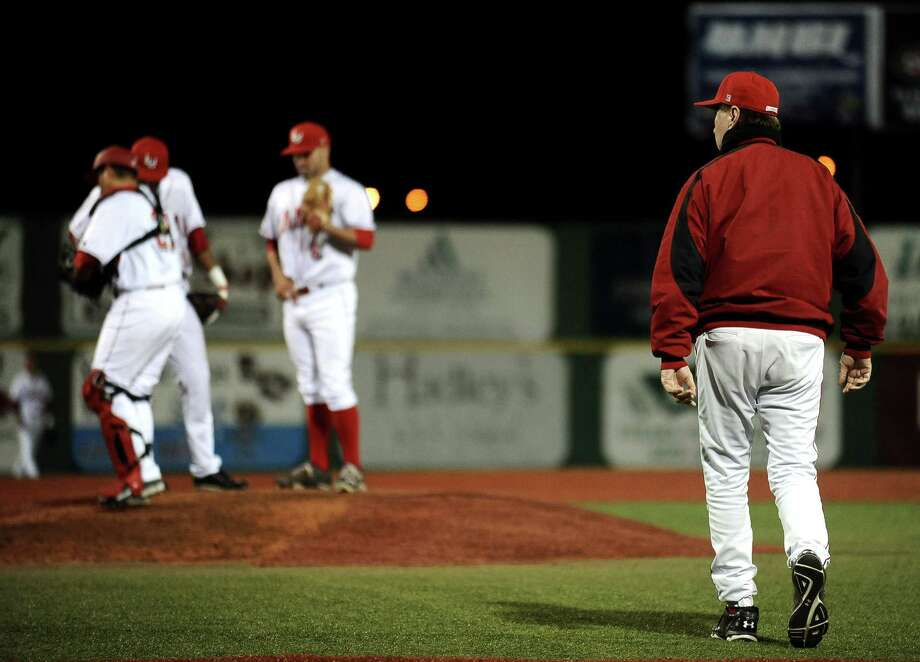 With the bases loaded in the top of the 6th inning Lamar pitcher Eric Harrington, #6, walks a player forcing Coach Jim Gilligan onto the field during the Lamar University baseball game against University of Massachusetts at Vincent-Beck Stadium on Friday, March 8, 2013. Photo taken: Randy Edwards/The Enterprise Photo: Randy Edwards