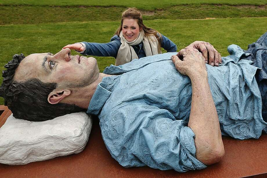 """The giant in the garden:Jessica Mander touches the schnoz of """"Catafalque"""" as if checking for breath on the grounds of the Glyndebourne Opera House in Lewes, England. The oversized reclining figure is by British artist Sean Henry. Photo: Dan Kitwood, Getty Images"""