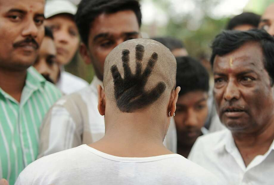 With his hair shorn in the symbol of the Congress Party, a party supporter attends the swearing-in of Karnataka Pradesh Congress Committee chief Siddaramaiah as Karnataka chief minister in Bangalore. Siddaramaiah led the party to a huge win in last week's assembly elections. Photo: Manjunath Kiran, AFP/Getty Images