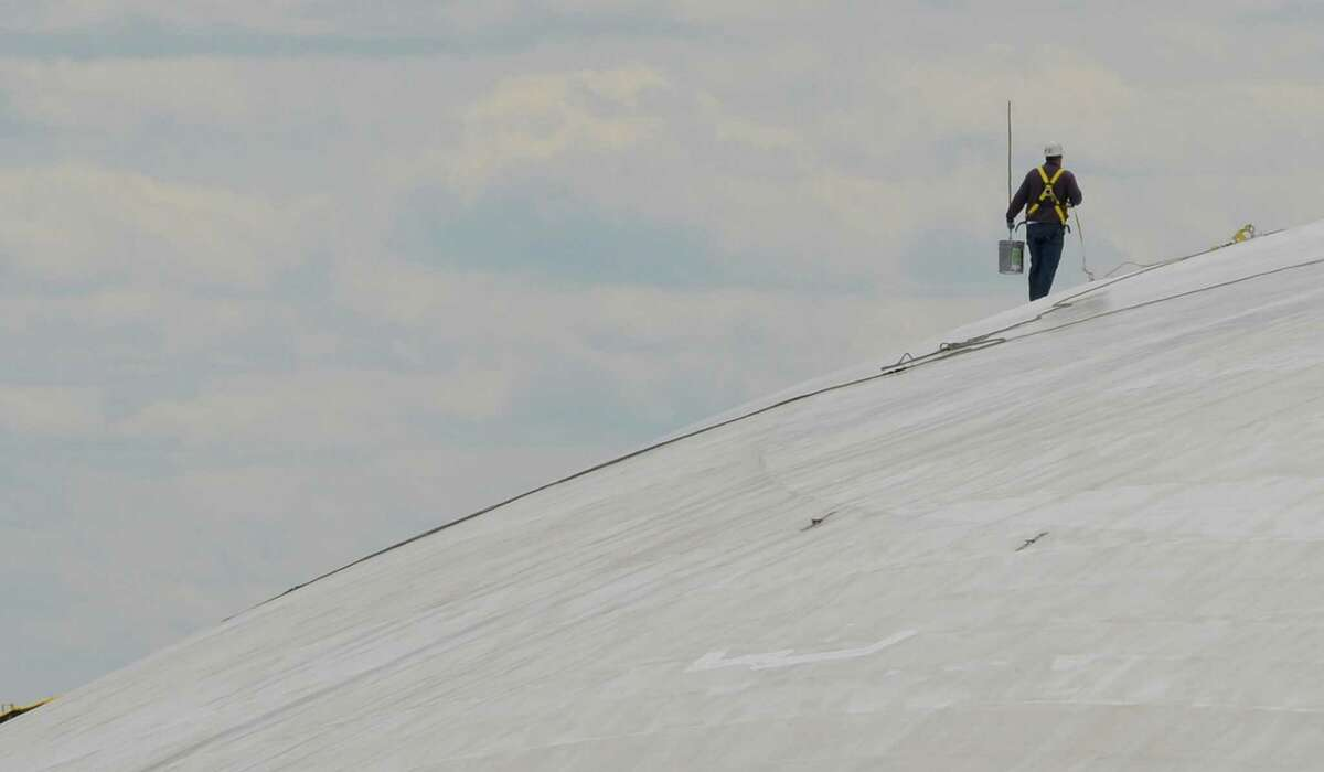 Workers clean and put a fresh coat of paint on the roof of the Egg on the Empire State Plaza on Tuesday, May 14, 2013, in Albany, N.Y. (Skip Dickstein/Times Union)