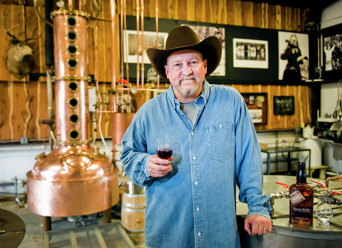 """Owner Dan Garrison holds a sample of bourbon in the distillery at Garrison Bros. Distillery in Hye, TX on Sat., Jan 12, 2013. At left stands """"Copper Cowgirl,"""" Garrison's first 100 gallon still. Ashley Landis for the Houston Chronicle"""