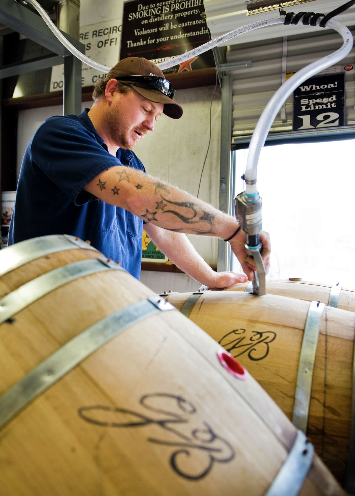 """Master distiller/distillery director Donnis Todd fills a barrel with """"white dog,"""" firmented bourbon before it's been aged, at Garrison Bros. Distillery in Hye, TX on Sat., Jan 12, 2013. Ashley Landis for the Houston Chronicle"""