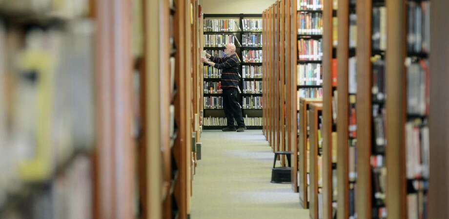 Ricardo Marlis, of Bethel, browses the fiction section of the Bethel Public Library in Bethel, Conn. on Tuesday, May 14, 2013.  The library closed down for six weeks to work on expansion, which was 13 years in the making.  The library made use of the previously empty second floor, doubling the space of the library and making room for more open reading and computer areas. Photo: Tyler Sizemore / The News-Times