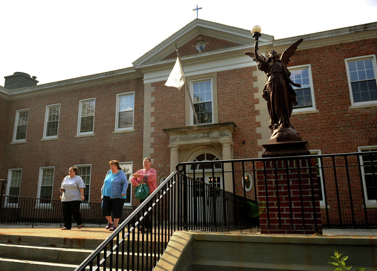 People exit The Catholic Center Diocese of Bridgeport at 238 Jewett Avenue in Bridgeport, Conn. on Tuesday, May 14, 2013.