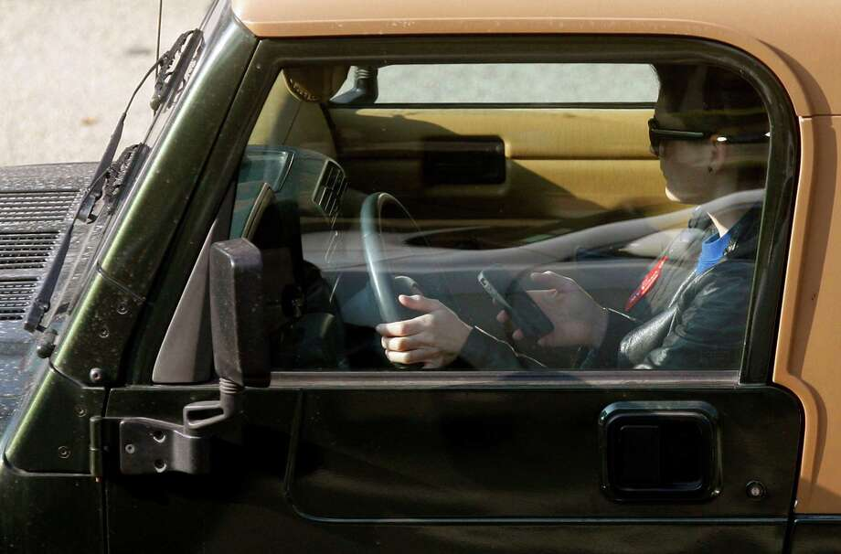 """FILE- In this Wednesday, Dec. 14, 2011, file photo, a driver uses an iPhone while driving Wednesday, in Los Angeles. The country's four biggest cellphone companies are set to launch their first joint advertising campaign against texting while driving, uniting behind AT&T's """"It Can Wait"""" slogan to blanket TV and radio during the summer of 2013. (AP Photo/Damian Dovarganes, File) Photo: Damian Dovarganes, STF / AP"""