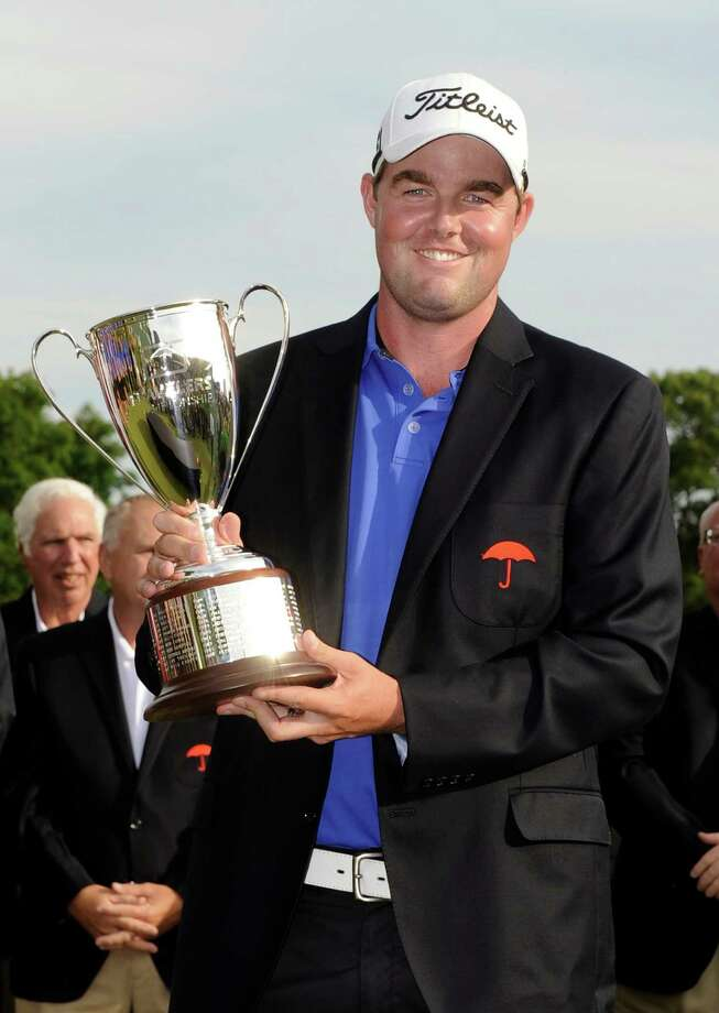FILE - In this June 24, 2012, file photo, Marc Leishman, of Australia, celebrates with the trophy after winning the Travelers Championship golf tournament in Cromwell, Conn.  When Leishman heard about the rampage in Newtown, he went to a map to see how far the school was from the course where months earlier he picked up his first PGA Tour victory. Next month, when he returns to defend his title, he wants to help in the healing process.  (AP Photo/Fred Beckham, File) Photo: Fred Beckham, Associated Press / FR153656 AP
