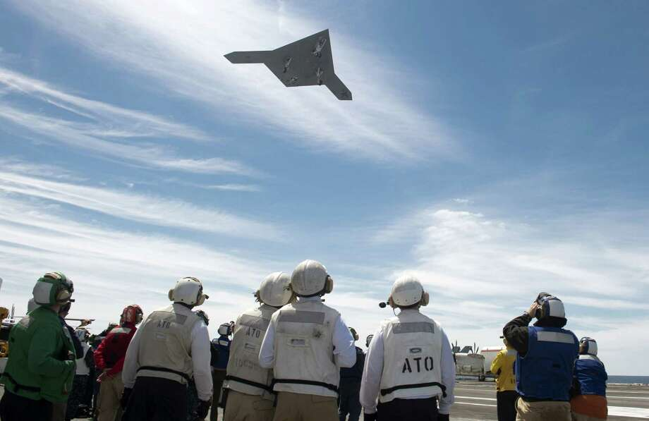 An unmanned X-47B  drone flies over the USS George H.W. Bush in the Atlantic Ocean on Tuesday. The aircraft carrier is the first to successfully catapult-launch an unmanned aircraft from its flight deck. Photo: U.S. Navy, Handout / 2013 U.S. Navy