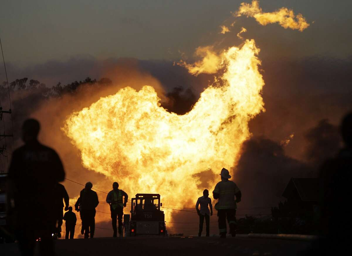 In this Sept. 9, 2010 file photo, a massive fire roars through a mostly residential neighborhood in San Bruno, Calif. The California agency investigating a deadly pipeline explosion and the City of San Bruno are set to propose major fines they say Pacific Gas & Electric Co. should pay for its negligence leading up to the blast. The City of San Bruno says the utility's shareholders should pay no less than $1.25 billion for violations regulators say PG&E committed before the 2010 explosion.