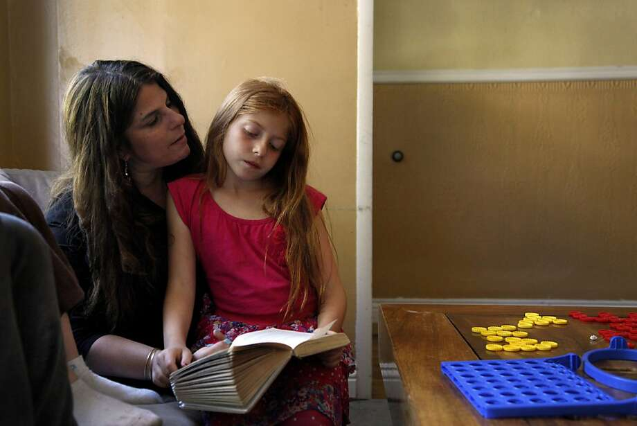 Beth Jaeger-Skigen reads with her daughter, Hana, 8, after school. The San Francisco woman opted to have her ovaries and breasts removed after genetic testing showed a high cancer risk. Photo: Preston Gannaway, Special To The Chronicle