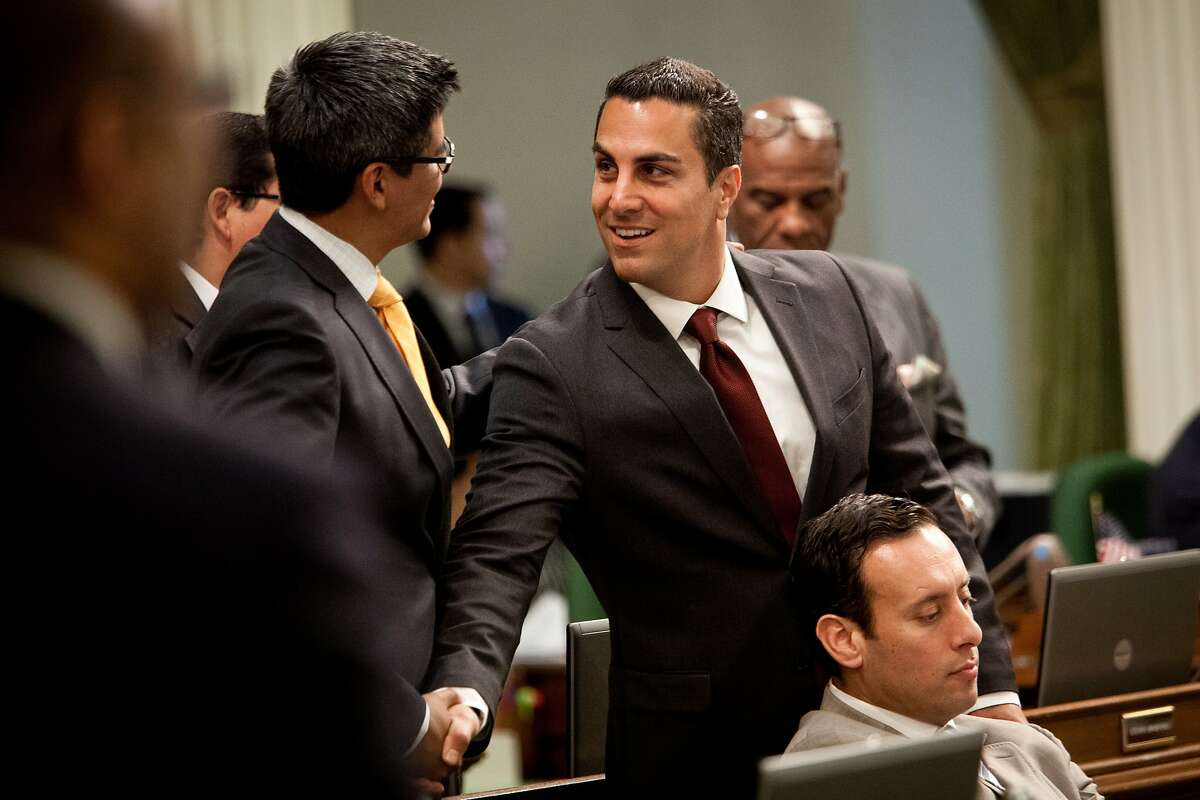 California State Assemblymember Henry Perea, left, greets Assemblymember Mike Gatto, right, during a legislative session in Assembly chambers at the State Capitol in Sacramento, California, April 29, 2013.