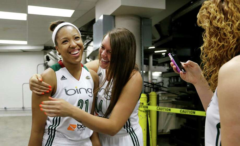 Seattle Storm's Tianna Hawkins, left, laughs with Cierra Bravard after having their photo taken by Chelsea Poppens, right, Tuesday, May 14, 2013, during the team's media day in Seattle. The Storm opens their WNBA basketball season Sunday, May 26, at Los Angeles. Photo: Elaine Thompson, AP / AP