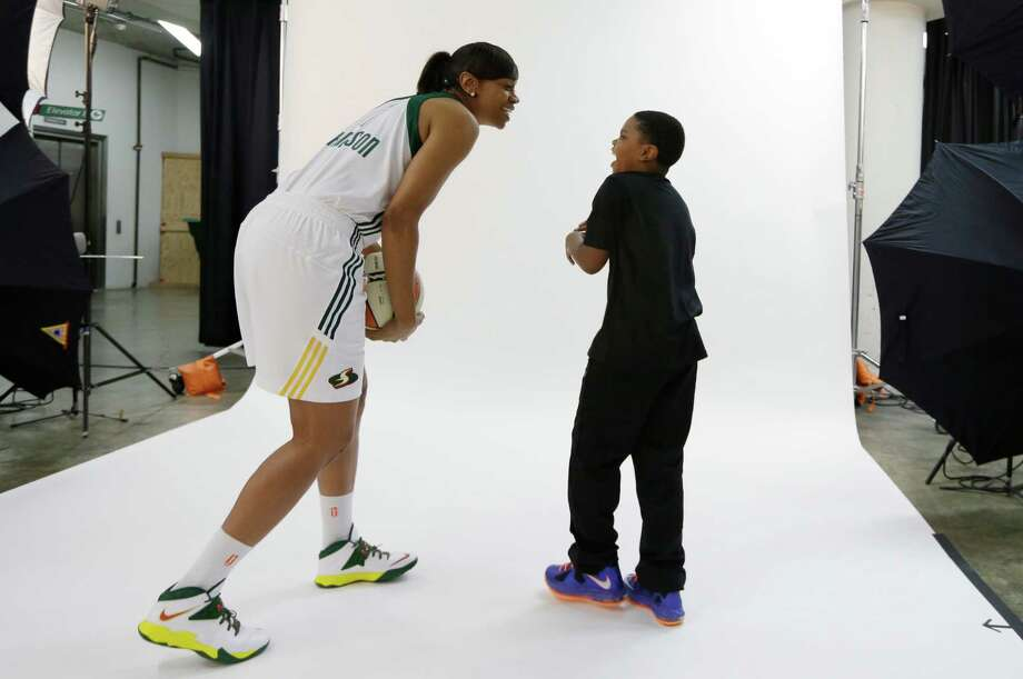 Seattle Storm's Tina Thompson laughs with her son, Dyllan Thompson Jones, 8, after the boy snuck up behind Thompson while she was being photographed Tuesday, May 14, 2013 during the team's media day in Seattle. The Storm opens their regular season Sunday, May 26, at Los Angeles. Photo: Elaine Thompson, AP / AP