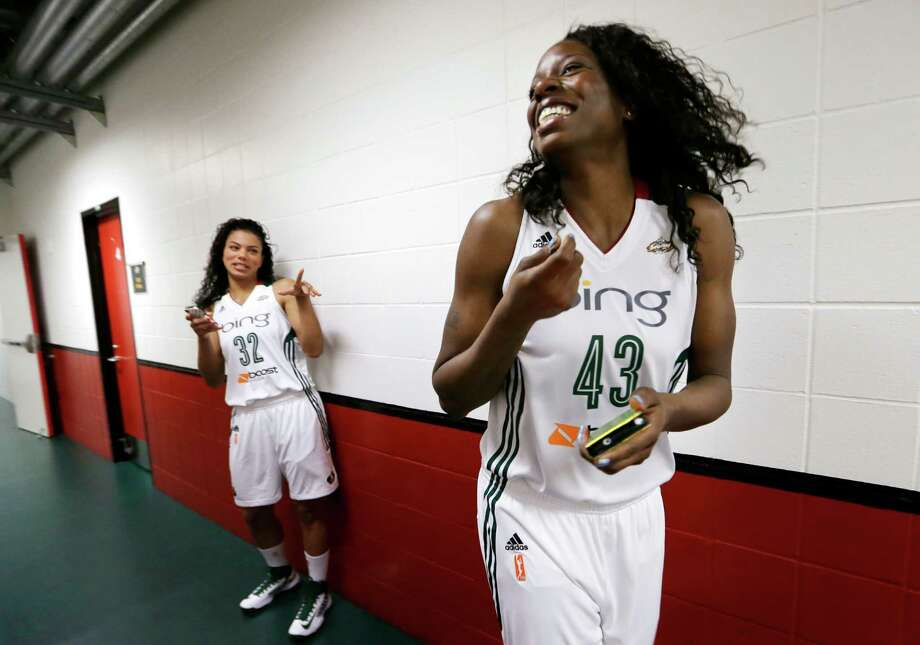 Seattle Storm's Nakia Sanford, right, smiles as she waits with Alysha Clark in a hallway Tuesday, May 14, 2013, during the team's media day in Seattle. The Storm opens their WNBA basketball season Sunday, May 26, at Los Angeles. Photo: Elaine Thompson, AP / AP