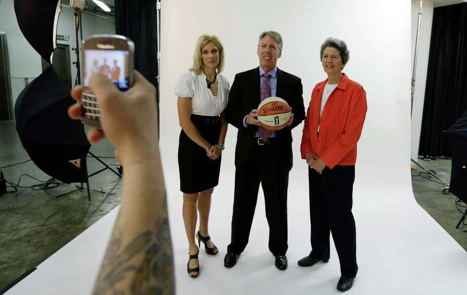 Seattle Storm head coach Brian Agler, center, is photographed on his cell phone with assistant coaches Jenny Boucek, left, and Nancy Darsch, Tuesday, May 14, 2013, at the team's media day in Seattle. The Storm opens their WNBA basketball season Sunday, May 26, at Los Angeles. Photo: Elaine Thompson, AP / AP