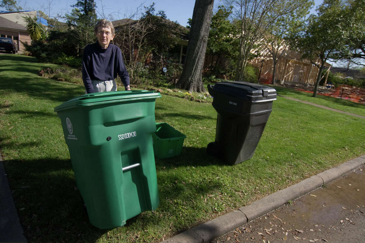 Julie Souchek shows the new green recycling container she and her neighbors received for use in Houston's curbside recycling program in this 2010 photo. Many residents in the Westridge neighborhood began using the containers immediately, although the program for which they are intended did not begin until April. Photo by R. Clayton McKee
