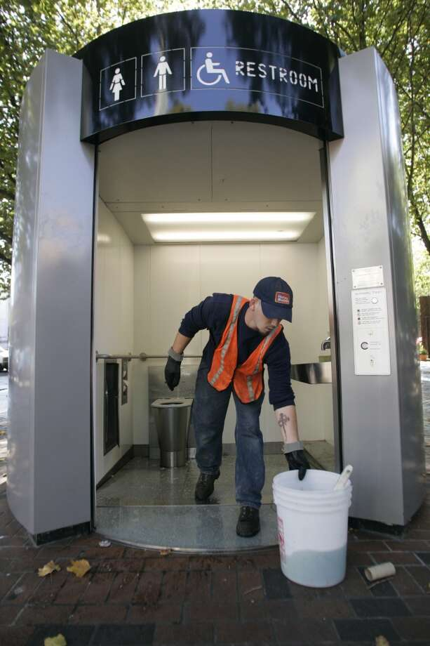 The toilets soon became havens for prostitutes and drug users and dealers as a clean, private place for business. Pictured is a Honey Bucket driver cleaning a toilet in Occidental Square in 2006. Photo: MIKE KANE, SEATTLE PI