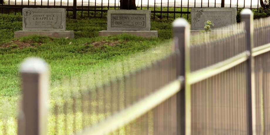 Three headstones line up in a neatly kept lot Tuesday on Houston Avenue that was set up like a graveyard in an attempt to keep vagrants from trashing the property. Photo: Billy Smith II / © 2013 Houston Chronicle