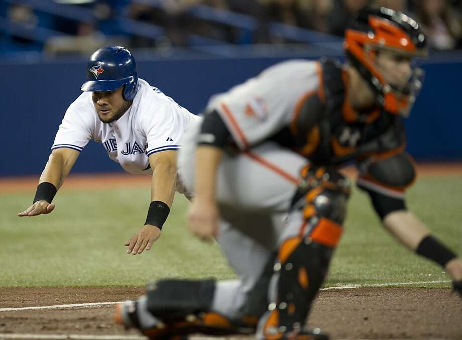 Toronto outfielder Melky Cabrera dives into home plate to score behind Giants catcher Buster Posey during the Blue Jays' six-run first inning. Photo: Frank Gunn, Associated Press