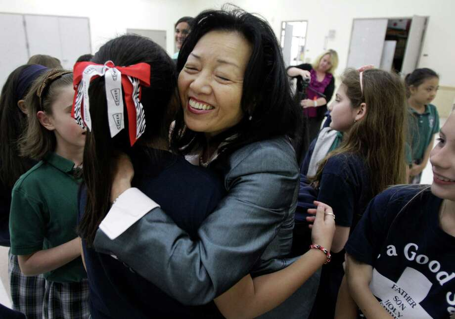 "Fourth-graders at St. Elizabeth Ann Seton Catholic School hug Dr. Ritsuko Komaki after her program Wednesday.  The class read the book ""Sadako and the Thousand Paper Cranes,"" about a Hiroshima victim who developed radiation induced leukemia. Photo: Melissa Phillip, Staff / © 2013  Houston Chronicle"