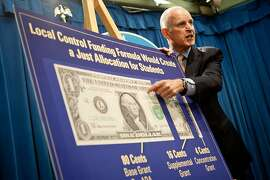Gov. Jerry Brown points to a graph detailing increased school spending during a press conference.
