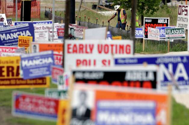 With campaign signs sprinkled throughout the area, readers join in the effort to support their candidates. (AP Photo/Eric Gay) Photo: Associated Press / AP