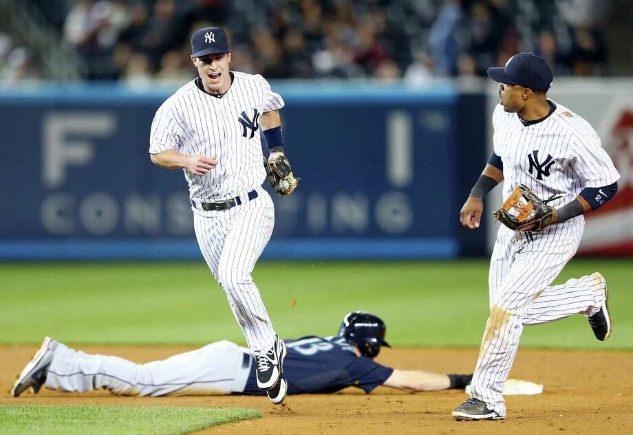 The Yankees' Jayson Nix, left, and Robinson Cano enjoy the turn of events as the Mariners' Dustin Ackley is doubled off second on a line drive to end the eighth. Photo: Elsa, Staff / 2013 Getty Images