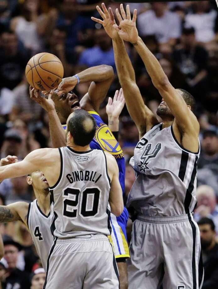 A trio of Spurs, including Manu Ginobili (20), harass Warriors forward Carl Landry. Photo: Eric Gay, STF / AP