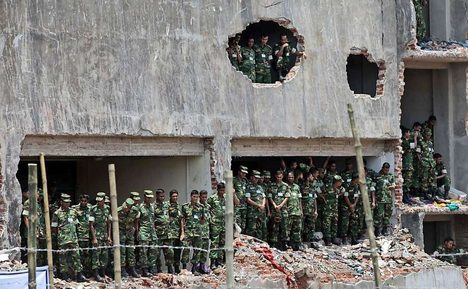Bangladesh army soldiers stand at the wreckage of a Bangladeshi garment factory building to offer prayers for the souls of the 1,127 people who died in the structure's collapse last month, in Savar, Bangladesh, Tuesday, May 14, 2013. The Islamic prayer service was held a day after the army ended the nearly three-week, painstaking search for bodies among the rubble of the worst tragedy in the history of the global garment industry and turned control of the site over to the civilian government for cleanup. (AP Photo/A.M. Ahad) Photo: A.M. Ahad, Associated Press