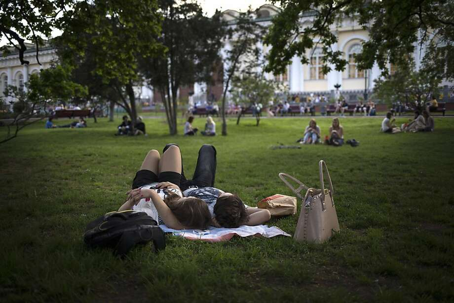 People have a rest after a sunny and hot day in Alexandrovsky park at the Kremlin in Moscow, Tuesday, May 14, 2013. On Tuesday unusually hot weather in Moscow, about 30 C (86 F)  broke a record of 28.4 C set on May 14, 1996. (AP Photo/Alexander Zemlianichenko) Photo: Alexander Zemlianichenko, Associated Press