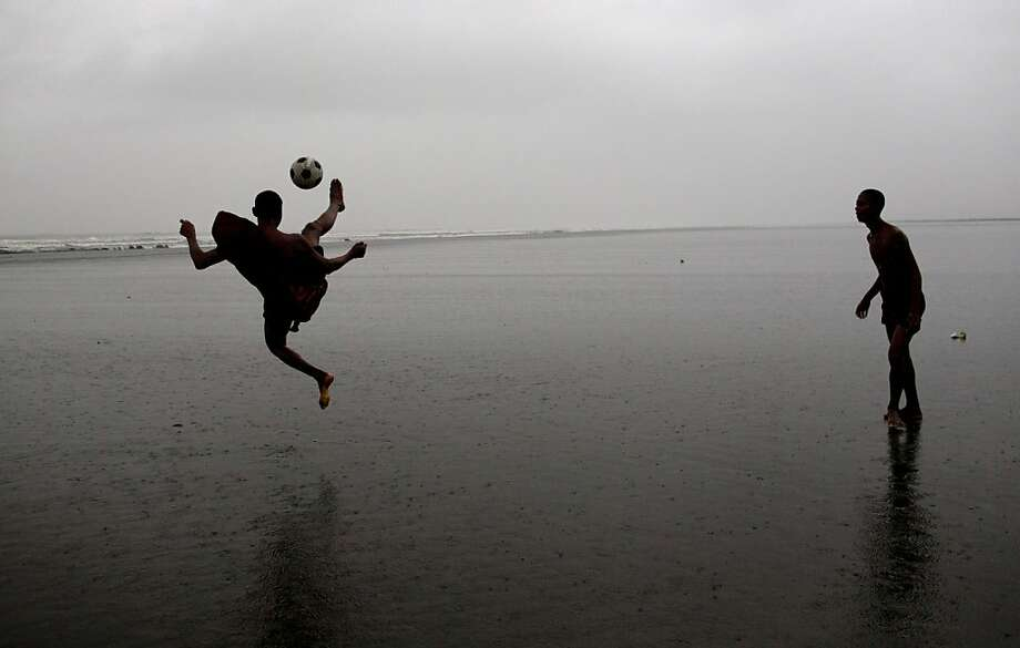 Novice Buddhist monks play soccer in shallow sea, Sittwe, northwestern Rakhine State, Myanmar, ahead of the arrival of Cyclone Mahasen, Tuesday, May 14, 2013. The U.N. said the cyclone, expected later this week, could swamp makeshift housing camps sheltering tens of thousands of Rohingya. Myanmar state television reported Monday that 5,158 people were relocated from low-lying camps in Rakhine state to safer shelters. But far more people are considered vulnerable. (AP Photo/Gemunu Amarasinghe) (AP Photo/Gemunu Amarasinghe) Photo: Gemunu Amarasinghe, Associated Press