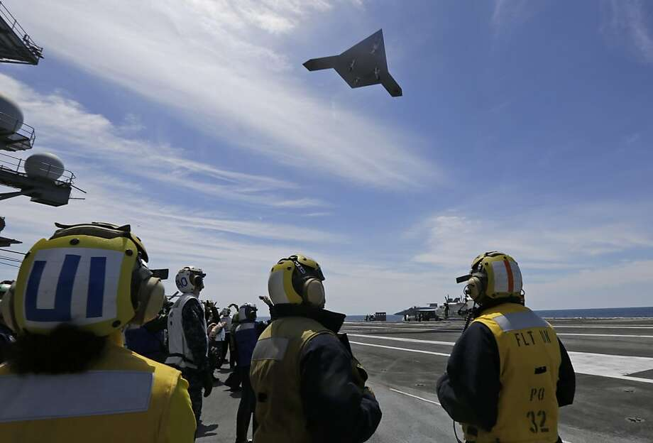 A Navy X-47B drone does a fly by the nuclear powered aircraft carrier USS George H. W. Bush after it was launched from the carrier off the coast of Virginia, Tuesday, May 14, 2013. (AP Photo/Steve Helber) Photo: Steve Helber, Associated Press