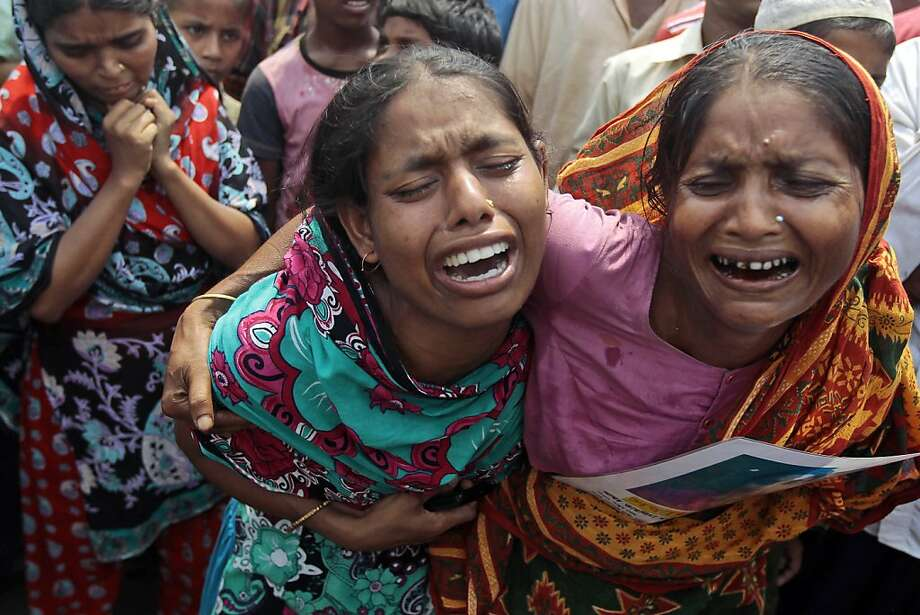 Bangladeshi women cry for their missing relatives during a prayer ceremony for the souls of the 1,127 people who died in a garment building structure collapse last month, in Savar, near Bangladesh, Tuesday, May 14, 2013. The Islamic prayer service was held a day after the army ended the nearly three-week, painstaking search for bodies among the rubble of the worst tragedy in the history of the global garment industry and turned control of the site over to the civilian government for cleanup. (AP Photo/A.M. Ahad) Photo: A.M. Ahad, Associated Press