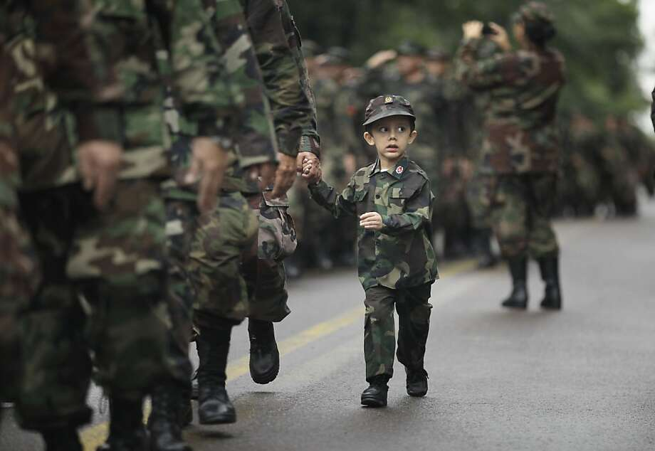 A child march with his father, a reservist of Paraguay's Army, during Independence Day parade in Asuncion, Paraguay, Tuesday, May 14, 2013. Paraguay commemorating 202 years of independence from Spanish rule. (AP Photo/Jorge Saenz) Photo: Jorge Saenz, Associated Press