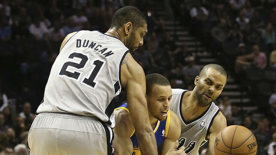 The Spurs' Tim Duncan (left) and Tony Parker clamp down on the Warriors' Stephen Curry during Game 5 on Tuesday at the AT&T Center.  Jerry Lara / San Antonio Express-News