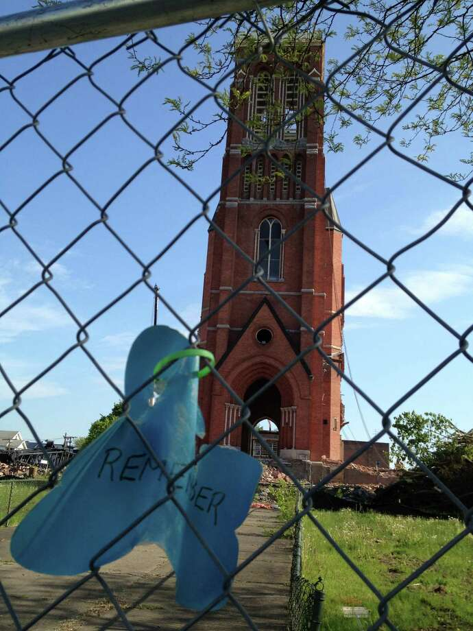 A message is left on the fence outside the remnants of St. Patrick's Church in Watervliet on Wednesday, May 15, 2013. A demolition crew will try to pull down the tower later in the day. (Mike Goodwin / Times Union)