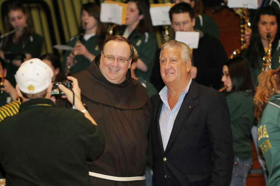 "With the Siena Pep Band playing in the background, Father Kevin Mullen, President of Siena College, left, poses for a photo with Albany City Mayor Jerry Jennings, right, as they nervously wait for the announcement of the Saints' seed and opponent in the upcoming NCAA Tournament, as the loyal crowd filled the gym on Sunday, March 14, 2010, during a ""Selection Sunday"" party in the ARC, on the Siena College Campus in Loudonville, NY.  The Saints were granted a 13th seed and will take on Fourth Seed, the Purdue Boilermakers, from the Big 10, on Friday in Spokane, Washington.    BASKETBALL COLLEGE SPORTS Photo: LUANNE M. FERRIS, TIMES UNION / 000007864A"