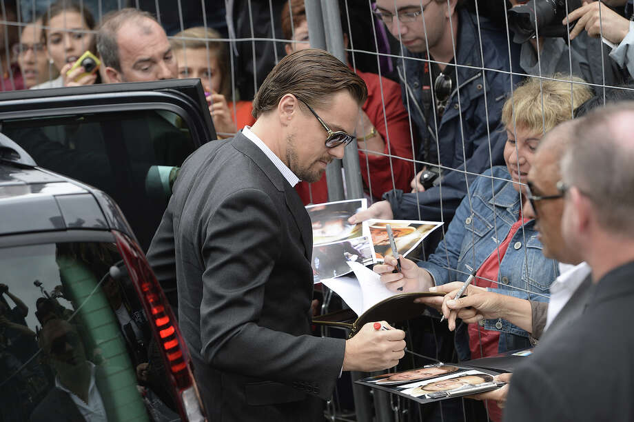"US actor Leonardo DiCaprio signs autographs as he arrives on May 15, 2013 for a photocall for ""The Great Gatsby"" ahead of the opening of the 66th edition of the Cannes Film Festival on May 15, 2013 in Cannes. Cannes, one of the world's top film festivals, opens on May 15 and will climax on May 26 with awards selected by a jury headed this year by Hollywood legend Steven Spielberg. Photo: ANNE-CHRISTINE POUJOULAT, AFP/Getty Images / 2013 AFP"