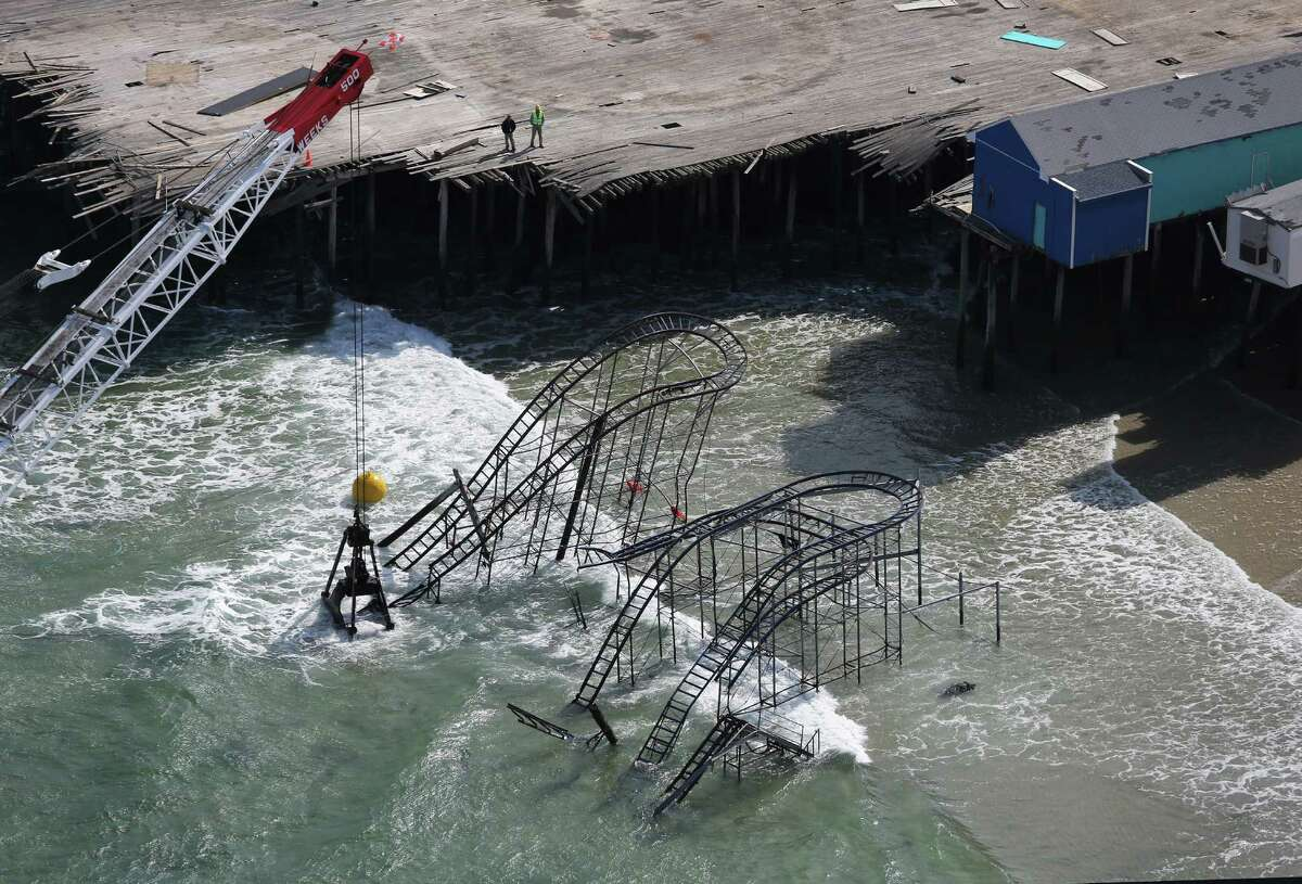 SEASIDE HEIGHTS, NJ - MAY 14: A crane demolishes the JetStar roller coaster more than 6 months after it fell into the ocean during Superstorm Sandy on May 14, 2013 in Seaside Heights, New Jersey. The Casino Pier contracted Weeks Marine to remove the wreckage of the iconic roller coaster from the surf.