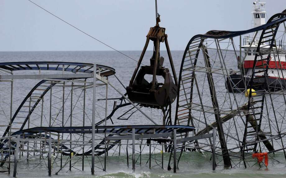 The claw of a crane, center, tears through the structure of the Jet Star Roller Coaster, Tuesday, May 14, 2013, in Seaside Heights, N.J. Workers began to demolish the roller coaster, which fell in the ocean when part of the Casino Pier was washed away by Superstorm Sandy in October. Photo: Julio Cortez, AP / AP