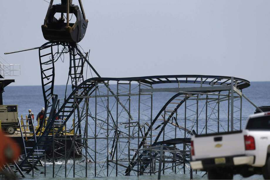 The claw of a crane, left, tears through the structure of the Jet Star Roller Coaster, Tuesday, May 14, 2013, in Seaside Heights, N.J. Workers began to demolish the roller coaster, which fell in the ocean when part of the Casino Pier was washed away by Superstorm Sandy in October. Photo: Julio Cortez, AP / AP