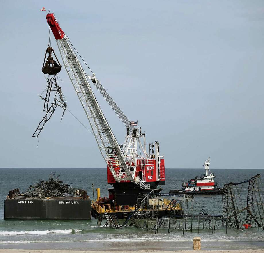 SEASIDE HEIGHTS, NJ - MAY 14:  A large crane demolishes the JetStar roller coaster that has been in the ocean for six months after the Casino Pier is sat on collapsed when Superstorm Sandy hit, May 14, 2013 in Seaside Heights, New Jersey. The Casino Pier has contracted Weeks Marine to remove the Jet Star roller coaster from the Atlantic Ocean. Photo: Mark Wilson, Getty Images / 2013 Getty Images